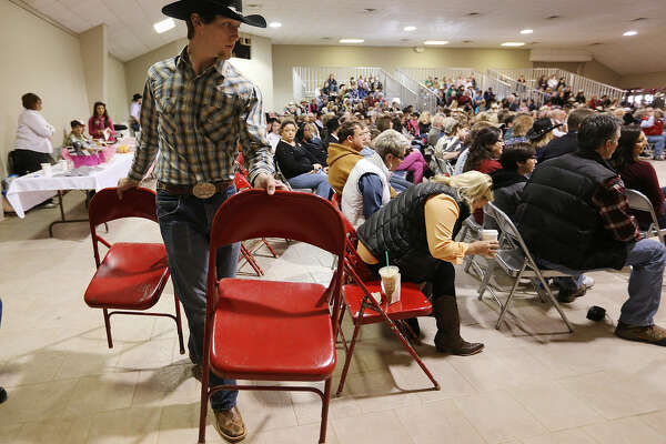 As the crowd increases, Cowboy Church volunteer Jared Maddox, 18, helps set up more chairs.