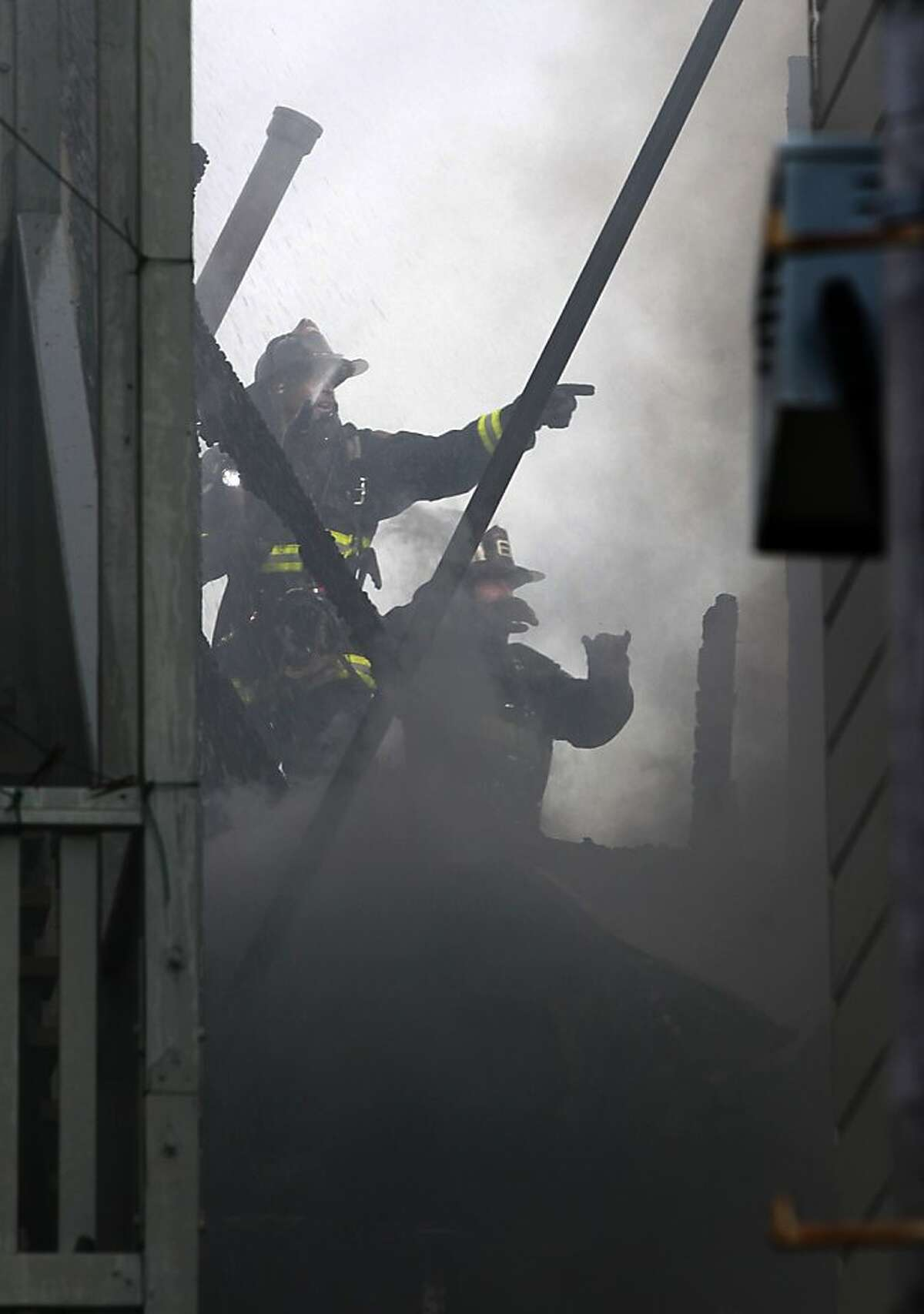 Firefighters work in a narrow space separating several structures while battling a 3-alarm blaze involving five apartment buildings at 23rd and Capp streets in San Francisco, Calif. on Saturday, Dec. 29, 2012. At least one firefighter was injured in the fire.