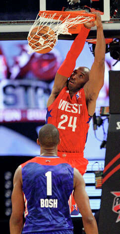 West's Kobe Bryant dunks as East's Chris Bosh looks on during second half action of the 62nd All-Star game at the Toyota Center Sunday Feb. 17, 2013 in Houston. The West won 143-138. Photo: Edward A. Ornelas, San Antonio Express-News / © 2013 San Antonio Express-News