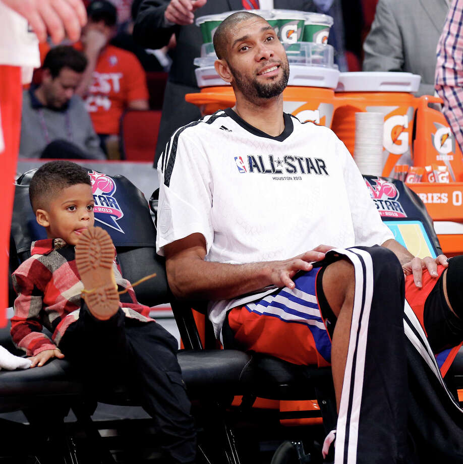 West's Tim Duncan sits on the bench with Chris Paul's son Chris Paul II, 3,  during halftime of the 62nd All-Star game at the Toyota Center Sunday Feb. 17, 2013 in Houston. Photo: Edward A. Ornelas, San Antonio Express-News / © 2013 San Antonio Express-News