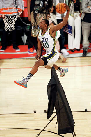 Utah Jazz's Jeremy Evans dunks over a painting during the Sprite Slam Dunk Contest at the Toyota Center Saturday, Feb. 16, 2013, in Houston. Photo: Edward A. Ornelas, San Antonio Express-News / © 2013 San Antonio Express-News
