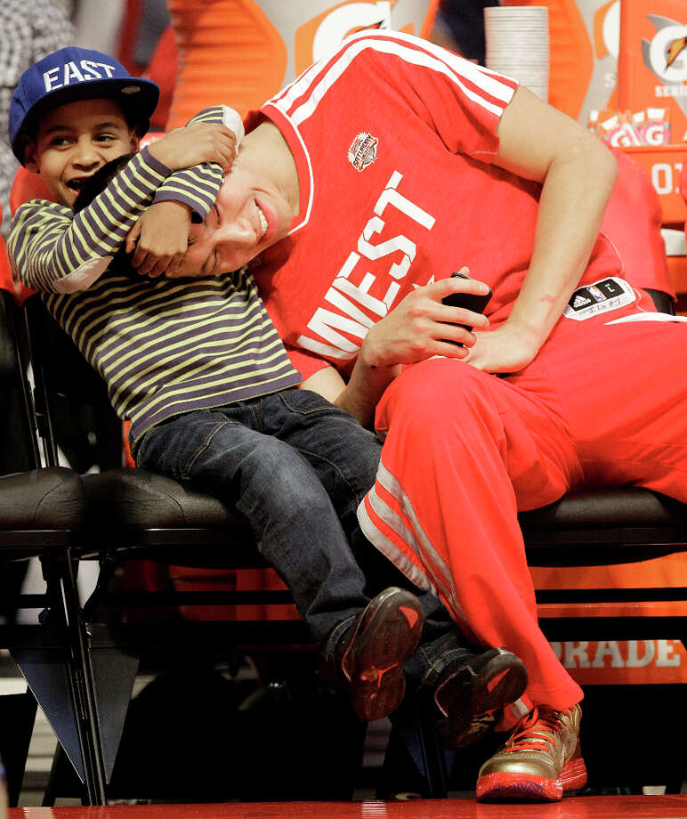 Jeremy Lin of the Houston Rockets plays with Kiyan Anthony, son of  Carmelo Anthony of the New York Knicks, after competing in the NBA All-Star Skills Challenge at the Toyota Center on All-Star Saturday Night, Saturday, Feb. 16, 2013, in Houston. Photo: Melissa Phillip, Houston Chronicle / © 2013  Houston Chronicle