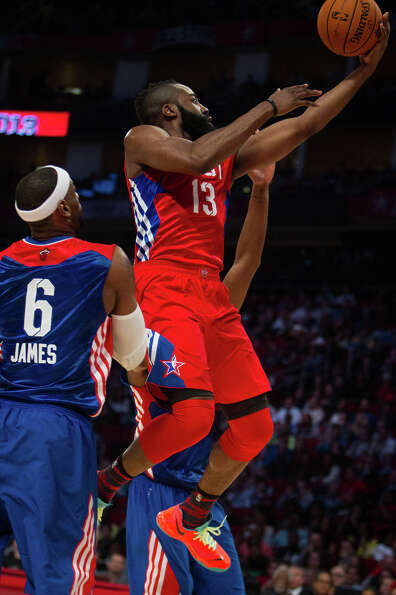James Harden of the Houston Rockets (13) drives past LeBron James of the Miami Heat (6).