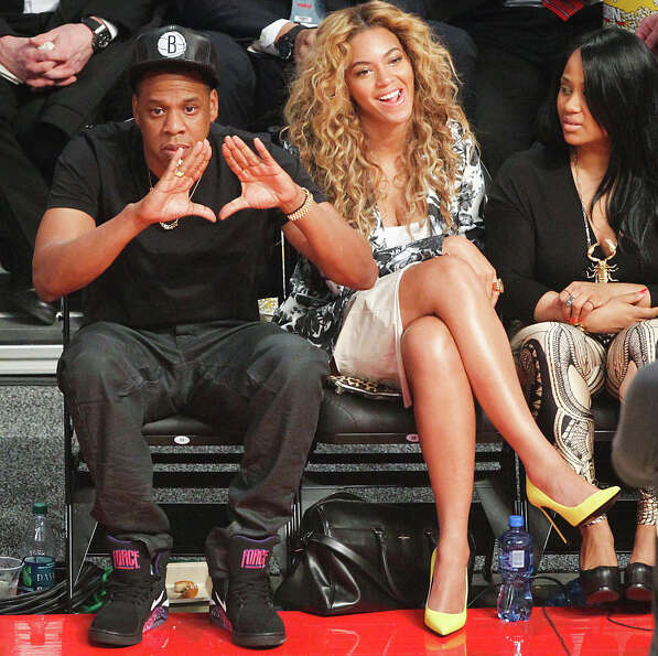 Jay-Z and Beyonce watch during the first half.