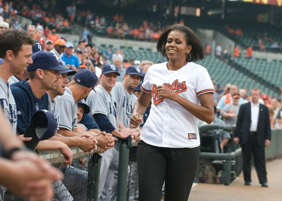 A FLOTUS ballpark appearance: First Lady Michelle Obama runs past the Tampa Bay Rays dugout after taking part in a ceremonial first pitch ceremony at Camden Yards in Baltimore on July 20, 2010. Photo: NICHOLAS KAMM, AFP/Getty Images / AFP