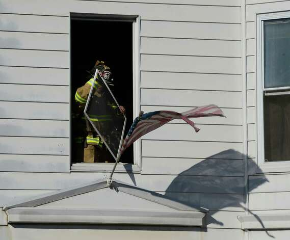 A firefighter removes a window from the fire building venting the remaining smoke after a fire struck 1817 4th Avenue Feb. 18, 2013, in Watervliet, N.Y. bringing mutual aid fire companies from Green Island and Troy.   (Skip Dickstein/Times Union) Photo: SKIP DICKSTEIN
