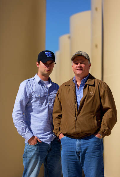 Andrew Fox, left, and his father, Nathan Fox, stand in front of some of the oil field tanks that the
