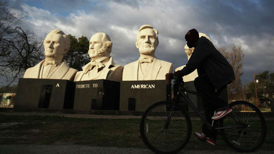 "A cyclist pedals past the 18 foot tall concrete sculptures of Stephen F. Austin, Sam Houston, Abraham Lincoln and George Washington created by Houston artist David Adickes at American Statesmanship Park, also known as ""Mount Rush Hour"", on Monday, Feb. 18, 2013, in Houston. Weather is expected to be in the high 60's today, mostly cloudy, and a chance of rain in the evening. Photo: . / © 2013 Houston Chronicle"