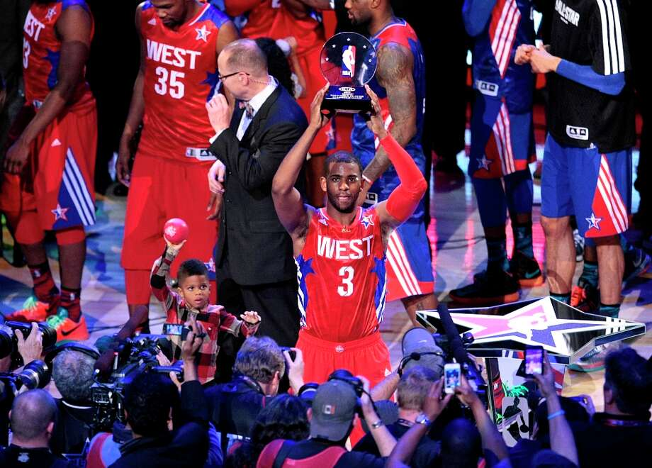 West 143, East 138Chris Paul of the Los Angeles Clippers holds up the game's MVP trophy. Photo: Billy Smith II / © 2013  Houston Chronicle