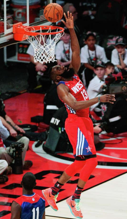 James Harden of the Houston Rockets (13) goes for a layup over Jrue Holiday of the Philadelphia 76ers (11). Photo: Billy Smith II, Houston Chronicle / © 2013  Houston Chronicle