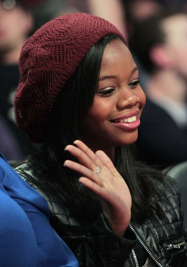 Olympic gold medalist Gabby Douglas waves to a tv camera during the first half of the NBA All-Star Game at the Toyota Center on Sunday, Feb. 17, 2013, in Houston. Photo: James Nielsen / © 2013  Houston Chronicle