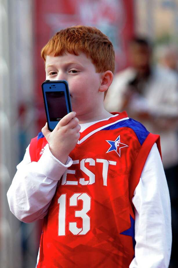 Kenny Lebowitz, 7, of Fort Lauderdale takes video on a cell phone as he waits in line to enter for the game. Photo: Melissa Phillip / © 2013  Houston Chronicle