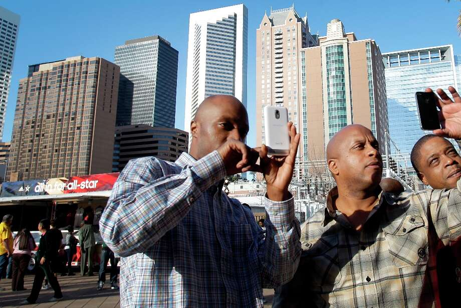 Zack Howell, left, of Youngstown, OH Scott Foster, center, of Houston and Jamal Perry, right, of Youngstown, OH take photos on cell phones outside at the Toyota Center. Photo: Melissa Phillip / © 2013  Houston Chronicle