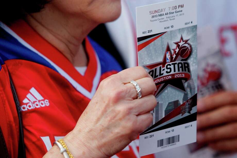 Fans show their tickets as they wait to enter Toyota Center. Photo: Melissa Phillip / © 2013  Houston Chronicle