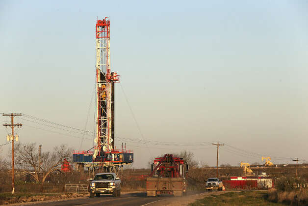 Traffic moves along FM 99 in Live Oak County near Whisett, Texas, past a Patterson-UTI drilling rig. Since 2010, Patterson-UTI has reported at least five fatal accidents involving