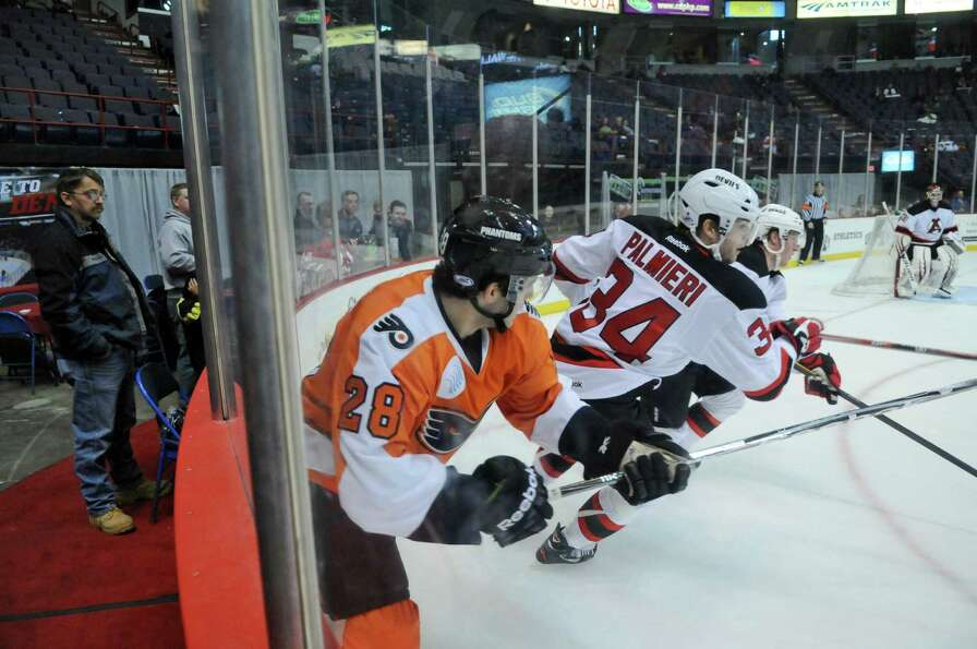 Adirondack Phantoms player Brandon Manning, left, and Albany Devils player Nick Palmieri head away f