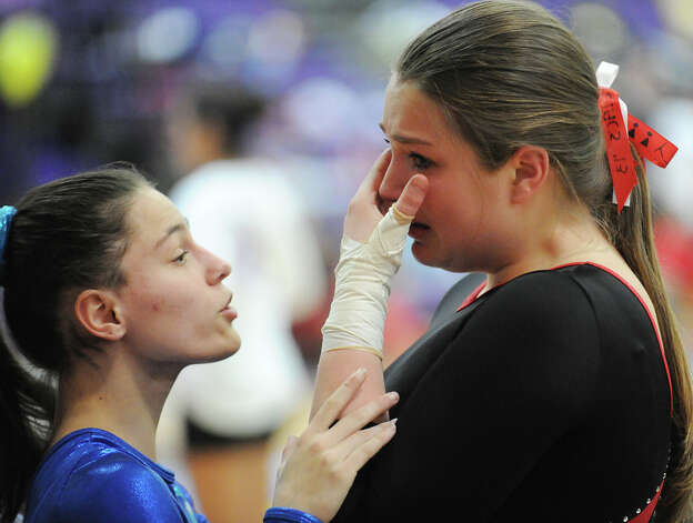 At left, Marya von Schmidt of Darien High School comforts New Canaan High School gymnast Raven Killinger during the 2013 FCIAC Girls Gymnastics Championships at Westhill High School in Stamford, Saturday, Feb. 16, 2013. Photo: Bob Luckey / Greenwich Time