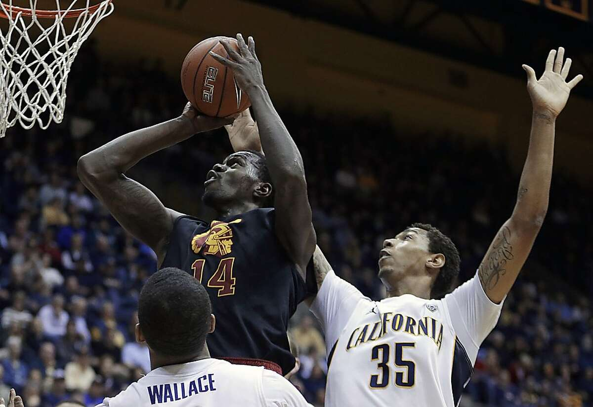 Southern California's Dewayne Dedmon (14) shoots over California's Richard Solomon (35) and Tyrone Wallace during the first half of an NCAA college basketball game, Sunday, Feb. 17, 2013, in Berkeley, Calif. (AP Photo/Ben Margot)