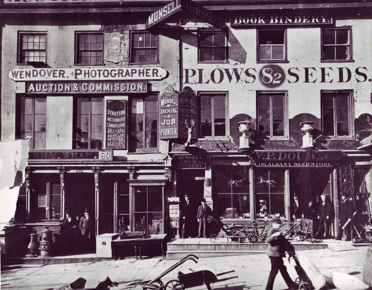 Photo Courtesy Albany Institute of History & Art Undated. Late 19th-century street scene along lower Broadway, featuring a phtoographer's and printer's shops, near what became known as Newspaper Row just off Broadway on Beaver Street.