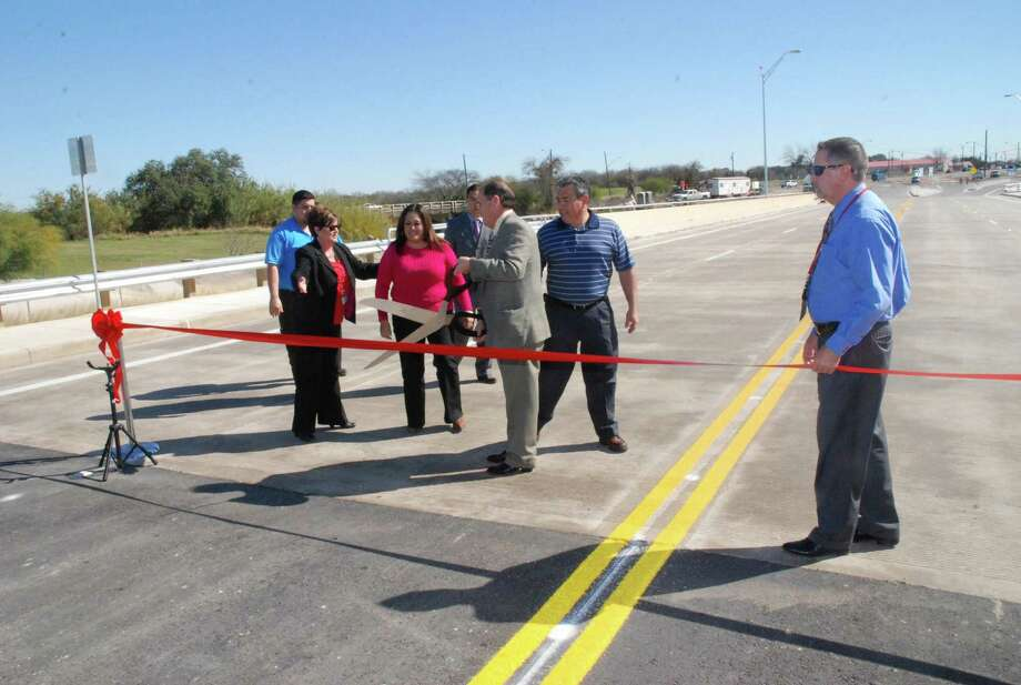"Precinct 1 Bexar County Commissioner Sergio ""Chico"" Rodriguez (with scissors) and county leaders recently cut the red ribbon and re-opened the South Flores Street Bridge to traffic. Photo: Steve Valdez/ For The Southside Reporter"