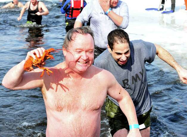 John Krupinsky comes out of the fresh water of Lake Kenosia with a live lobster in hand at the Jack Knapp Sr. Danbury Dip for Charity Saturday, Feb. 16, 2013, in Conn. Tom Saadi emerges at right. Photo: Michael Duffy / The News-Times