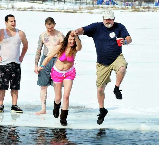 Cassie Mooris and Jerry Saville take the plunge into the icy waters of Lake Kenosia, outside the Moose Lodge, at the Jack Knapp Sr. Danbury Dip for Charity Saturday, Feb. 16, 2013, in Conn. Photo: Michael Duffy / The News-Times