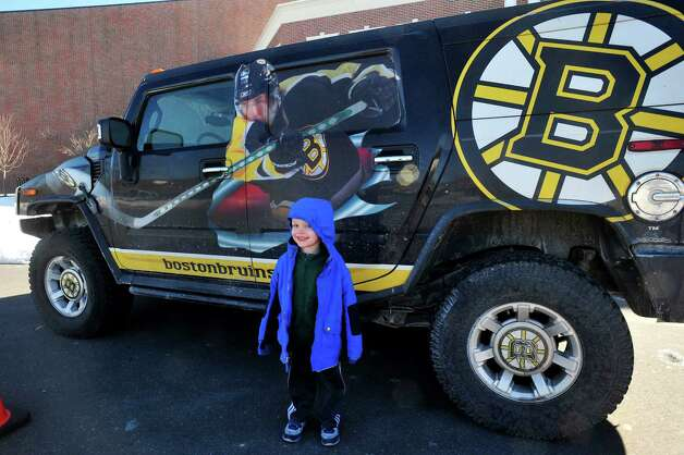 The Boston Bruins professional hockey team holds a street hockey clinic for kids at the Newtown Youth Academy Monday, Feb. 18, 2013 in Conn. Ethan Kravec, 5, of Newtown,  poses for his mom in front of the team car. Photo: Michael Duffy / The News-Times