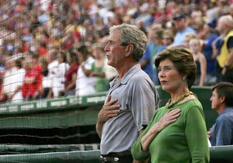 George and Laura Bush stand for the national anthem before a 2010 playoff game between the Texas Rangers and the New York Yankees. Photo: AP
