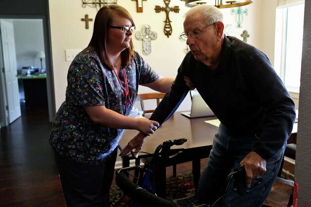 Kayla Hester, CNA, of Nurse Next Door home health care, helps George Roeber, 92, up from his seat after they played dominoes at his home in San Antonio on Friday, Feb. 1, 2013. Photo: Lisa Krantz, San Antonio Express-News / © 2012 San Antonio Express-News