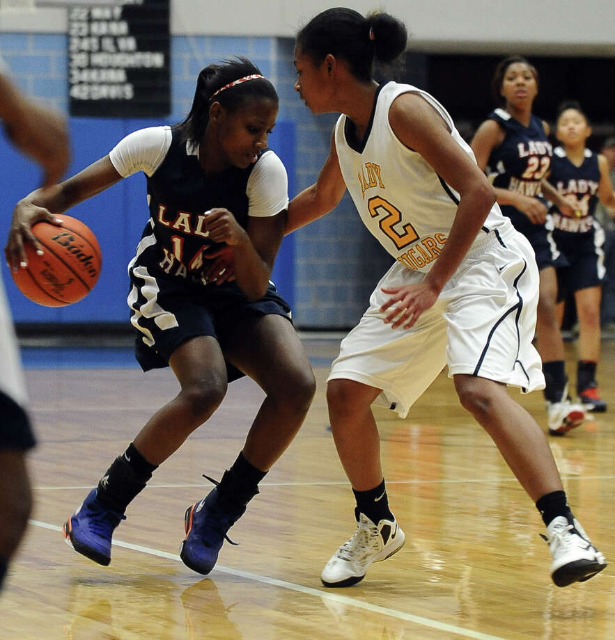 Lady Hawk Kesha Broussard, #14, shakes off Lady Cougar Ashley Pickney, #2, during the La Marque High School Lady Cougars Class 3A playoff girls basketball game against Hardin-Jefferson Lady Hawks at Barbers Hill High School on Thursday, February 14, 2013. Lady Cougars, 73 - 61. Photo taken: Randy Edwards/The Enterprise Photo: Randy Edwards