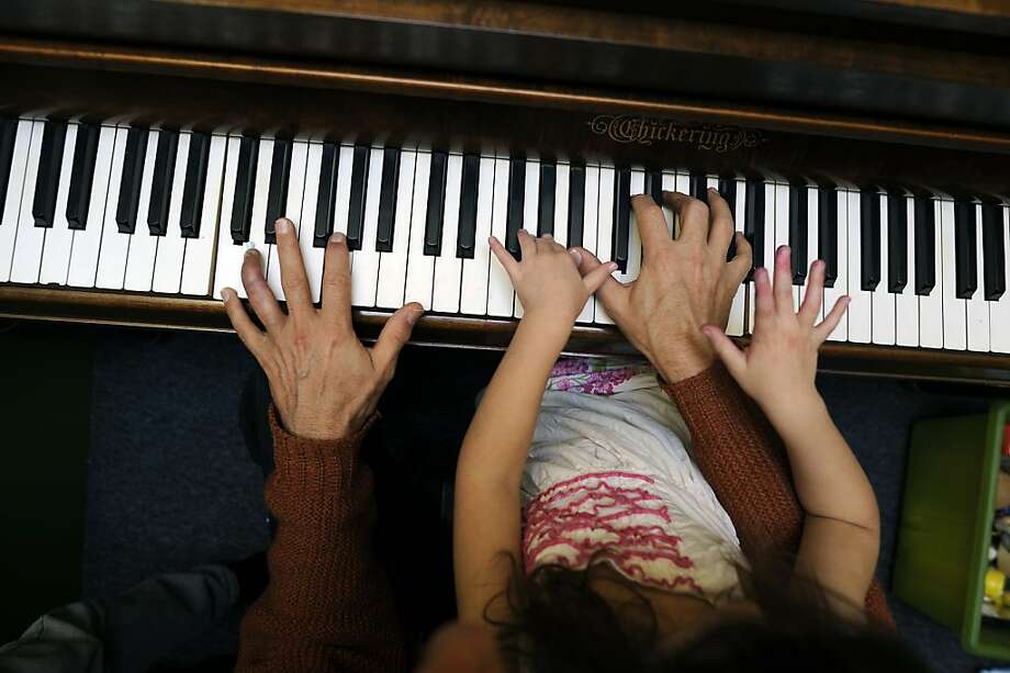 Christopher Schardt plays the piano with his daughter Ruby. He has regained the use of his damaged finger. Photo: Michael Short, Special To The Chronicle