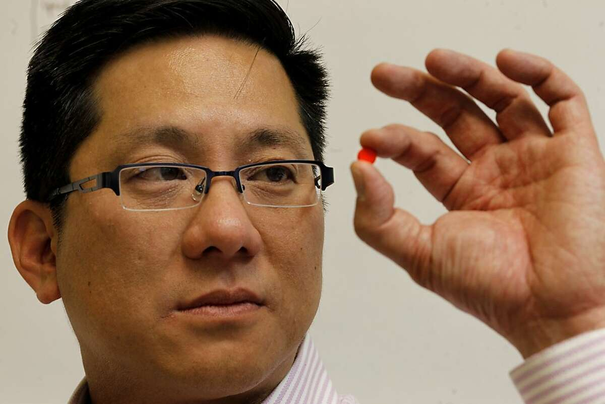 Peter Wong, the Chief Operating Officer of TruTag, looks at one of the pills that has his silicon coating Thursday February 14, 2013. TruTag Technologies of Oakland, Calif. and Hawaii, says they are the first edible code that can be put on pills to prove their authenticity for patients and pharmaceutical companies.
