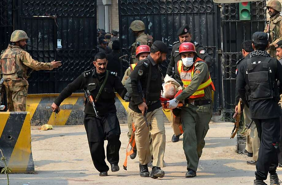 Security workers carry an injured man from the office of the top political official of the Khyber tribal region in Peshawar, Pakistan, after an attack. Photo: A Majeed, AFP/Getty Images