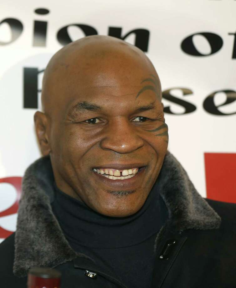 Former heavyweight champion Mike Tyson smiles during a promotional event for former five-time champion Evander Holyfield's Real Deal barbecue sauce at a Chicago grocery store Saturday, Feb. 16, 2013. (AP Photo/Charlie Arbogast) Photo: Charlie Arbogast, STF / AP