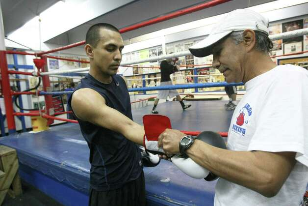 Antonio Juarez, 56, helps train his son James, 26, at Calderon, on the West Side. James Juarez will compete at 132 pounds in the novice division at the Golden Gloves competition. Photo: Helen L. Montoya, San Antonio Express-News / ©2013 San Antonio Express-News