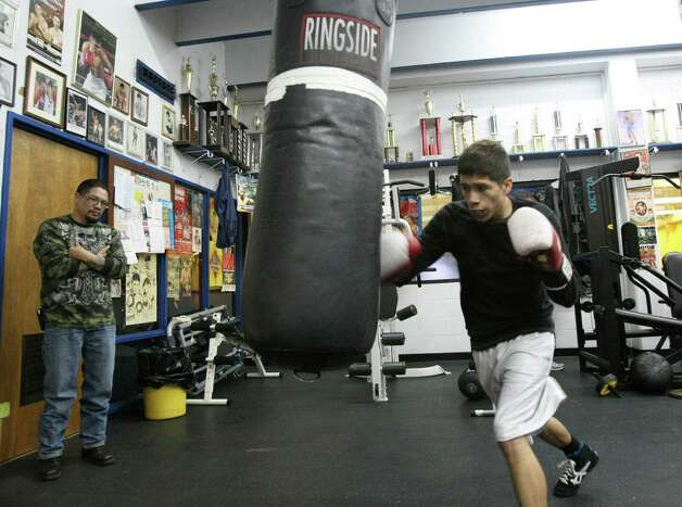 Johnny Garcia, 45, helps train his son Nicholas, 19, at Calderon Boys & Girls Club. The younger Garcia will be making his amateur debut in the local Golden Gloves tournament this week. Photo: Helen L. Montoya, San Antonio Express-News / ©2013 San Antonio Express-News