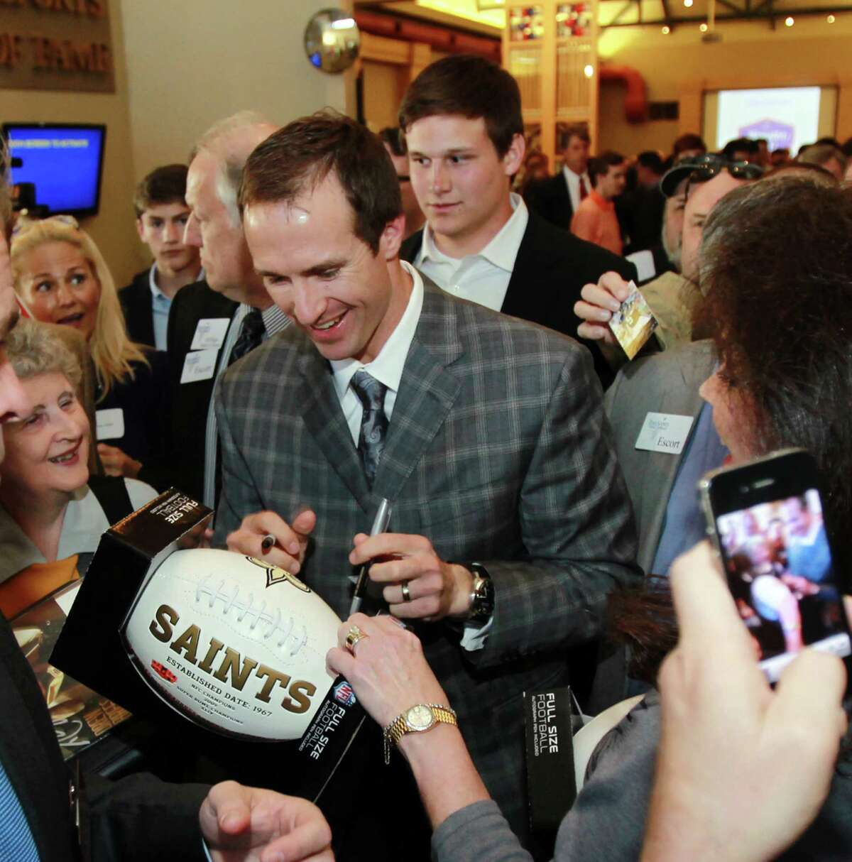 New Orleans Saints NFL football quarterback Drew Brees signs a football at a reception before the induction for the 2013 class of the Texas Sports Hall of Fame, Monday, Feb. 18, 2013, in Waco, Texas.