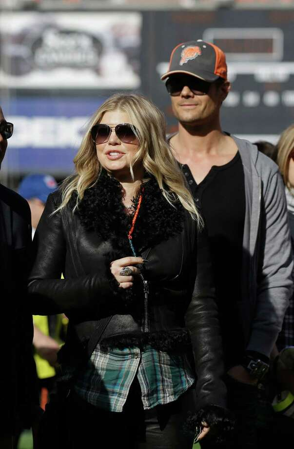 FILE--In this Dec. 9, 2012, file photo, Singer Fergie of the Black Eyed Peas  walks with her husband Josh Duhamel, right, on the sidelines during the first quarter of an NFL football game between the San Francisco 49ers and the Miami Dolphins in San Francisco. A representative for the Black Eyed Peas singer confirmed that Fergie is pregnant with her first child on Monday, Feb. 18, 2013. (AP Photo/Marcio Jose Sanchez, File) Photo: Marcio Jose Sanchez