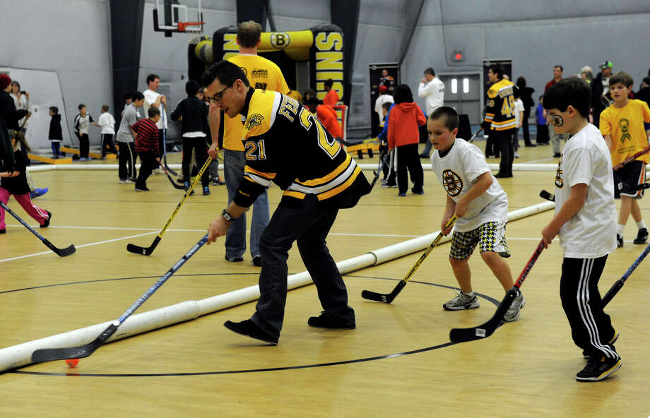 Boston Bruin player Andrew Ference works with kids at a hockey clinic Monday. The Boston Bruins hockey team held hockey clinics for Newtown kids at the Newtown Youth Academy, Monday, Feb. 18, 2013. Photo: Carol Kaliff / The News-Times