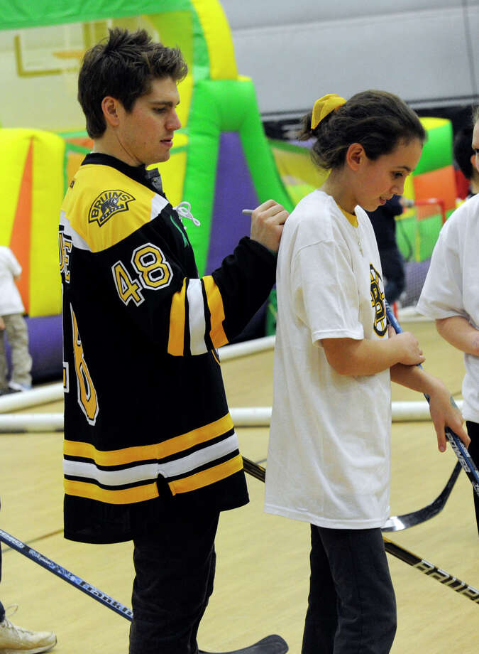 Chris Bourque, of the Boston Bruins, autographs a T-shirt Monday. The Boston Bruins hockey team held hockey clinics for Newtown kids at the Newtown Youth Academy, Monday, Feb. 18, 2013. Photo: Carol Kaliff / The News-Times