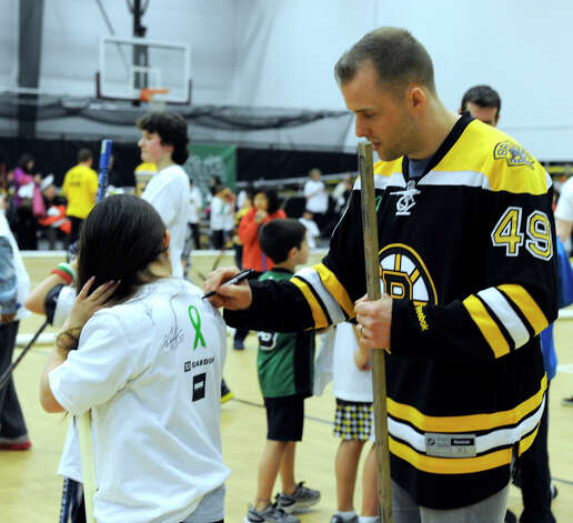 Boston Bruin player Rich Peverley signs autographs Monday. The Boston Bruins hockey team held hockey clinics for Newtown kids at the Newtown Youth Academy, Monday, Feb. 18, 2013.