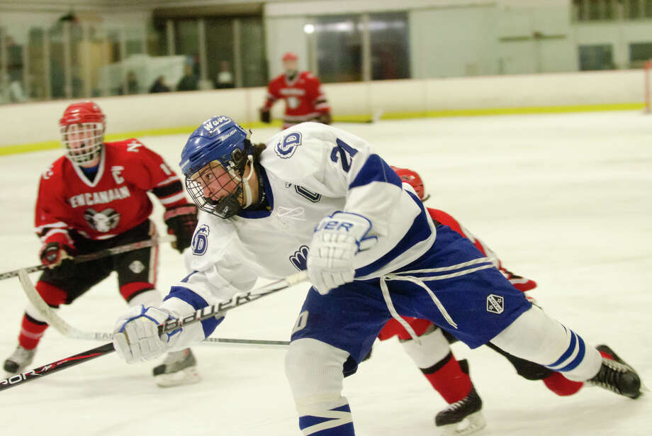 Darien's Brendan Hathaway (21) takes a shot on goal during the second period of the boys hockey game against New Canaan High School at Darien Ice Rink on Monday, Feb. 18, 2013. Photo: Amy Mortensen / Connecticut Post Freelance