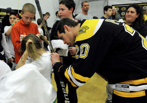 Boston Bruin playerDaniel Paille signs an autograph Monday. The Boston Bruins hockey team held hockey clinics for Newtown kids at the Newtown Youth Academy, Monday, Feb. 18, 2013. Photo: Carol Kaliff / The News-Times