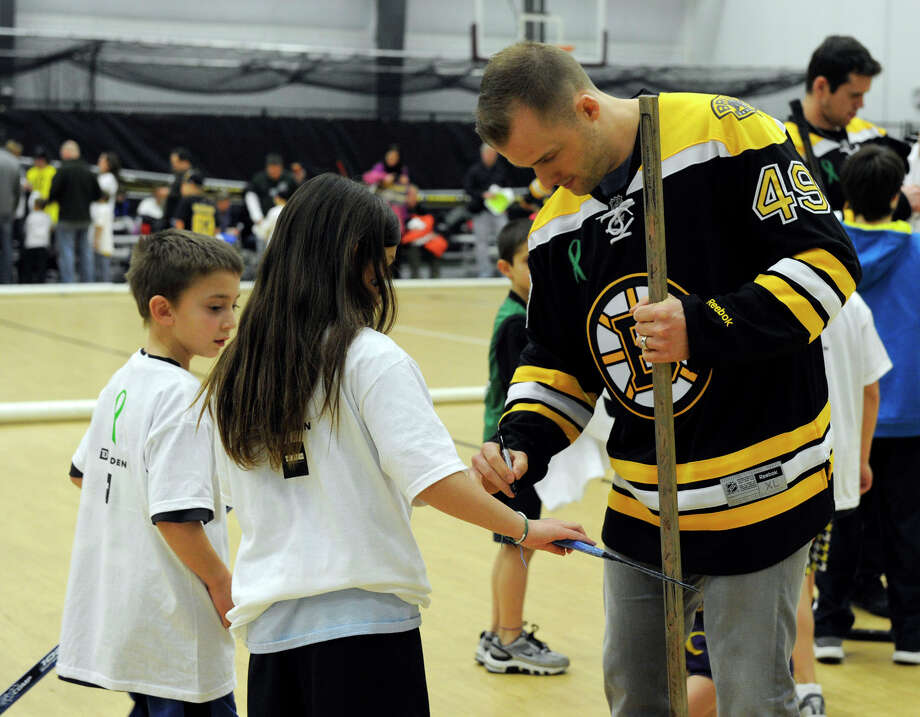 Boston Bruin player Rich Peverley signs autographs Monday. The Boston Bruins hockey team held hockey clinics for Newtown kids at the Newtown Youth Academy, Monday, Feb. 18, 2013. Photo: Carol Kaliff / The News-Times