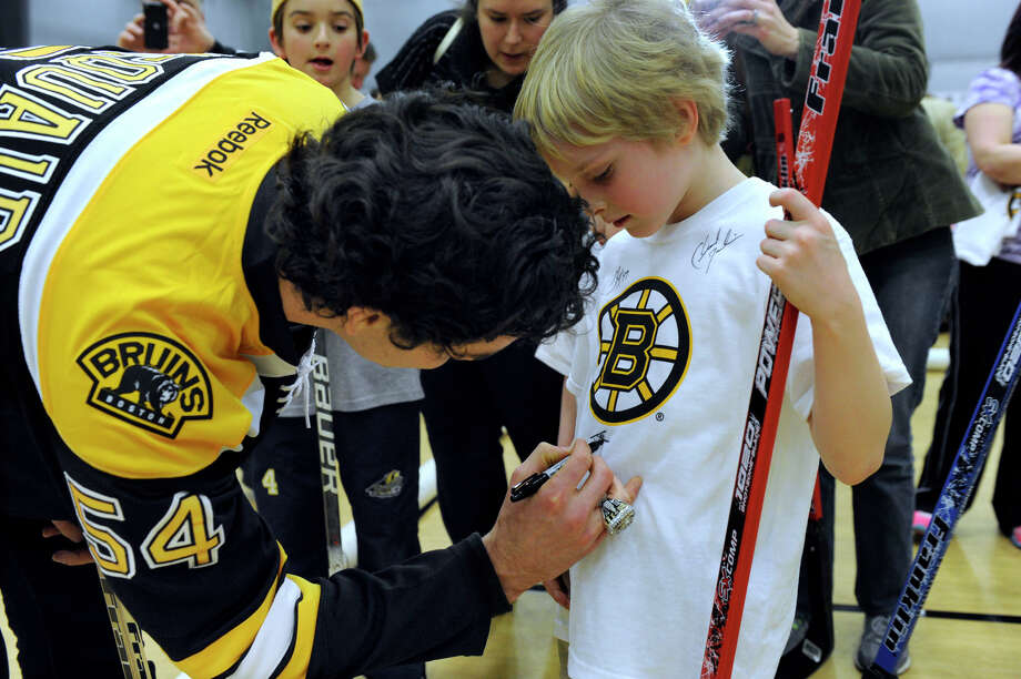 Adam McQuaid of the Boston Bruins hockey team signs an autograph for Gavin Johnson, 7, of Newtown Monday. The Boston Bruins held hockey clinics for Newtown kids at the Newtown Youth Academy, Monday, Feb. 18, 2013. Photo: Carol Kaliff / The News-Times