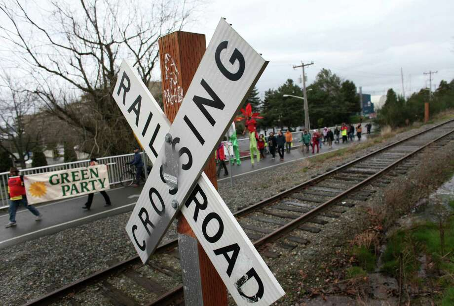 People cross railroad tracks during a protest against proposed coal trains that would pass through Seattle. The trains are part of a proposal to ship coal from the U.S. via rail to ships and eventually to Asia. Opposition to the plan has been fierce, especially in Western Washington. Photo: JOSHUA TRUJILLO / SEATTLEPI.COM