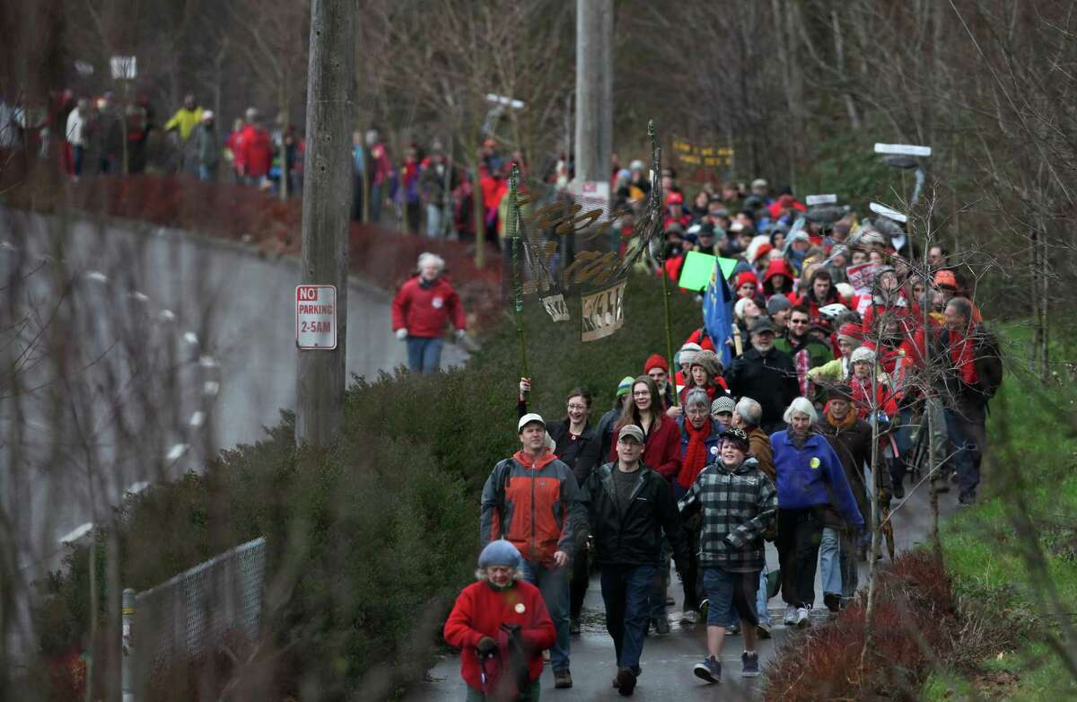 People march along the Burke-GIlman Trail during a protest against proposed coal trains that would pass through Seattle.The trains are part of a proposal to ship coal from the U.S. via rail to ships and eventually to China. Opposition to the plan has been fierce, especially in Western Washington.