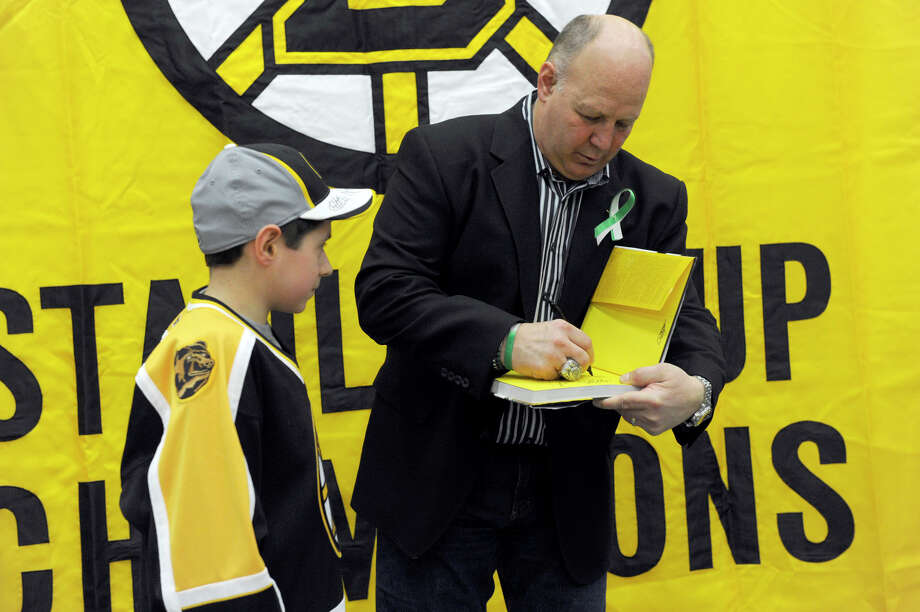 Claude Julien, head coach of the The Boston Bruins hockey team, signs an autograph for a fan Monday. The Boston Bruins held hockey clinics for Newtown kids at the Newtown Youth Academy, Monday, Feb. 18, 2013. Photo: Carol Kaliff / The News-Times