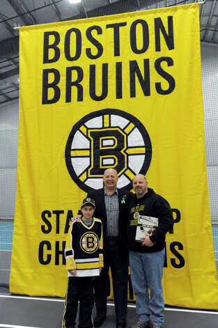 Claude Julien, head coach of the The Boston Bruins hockey team, poses for photos with fans Monday. The Boston Bruins held hockey clinics for Newtown kids at the Newtown Youth Academy, Monday, Feb. 18, 2013. Photo: Carol Kaliff / The News-Times