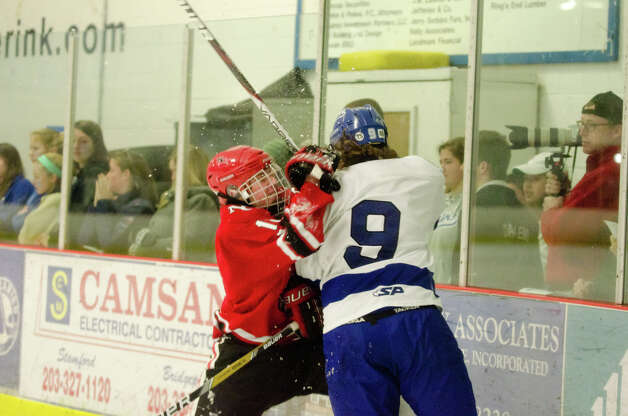 New Canaan's Peter Richardson (18) checks Darien's Dana Wensberg (9) during the boys hockey game at Darien Ice Rink on Monday, Feb. 18, 2013. Photo: Amy Mortensen / Connecticut Post Freelance